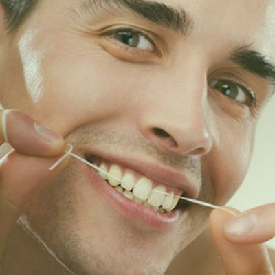 Image of a man flossing. This icon is for Outdoor Dental's list of dental health FAQ's