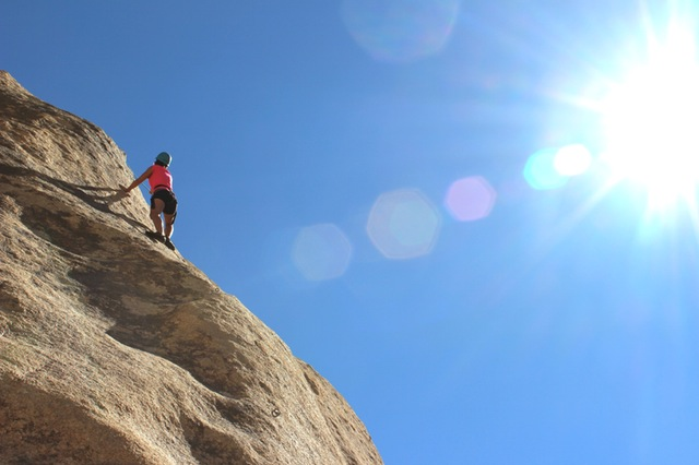 Image of a woman climbing a mountain. This is the perfect metaphor for dental anxiety.
